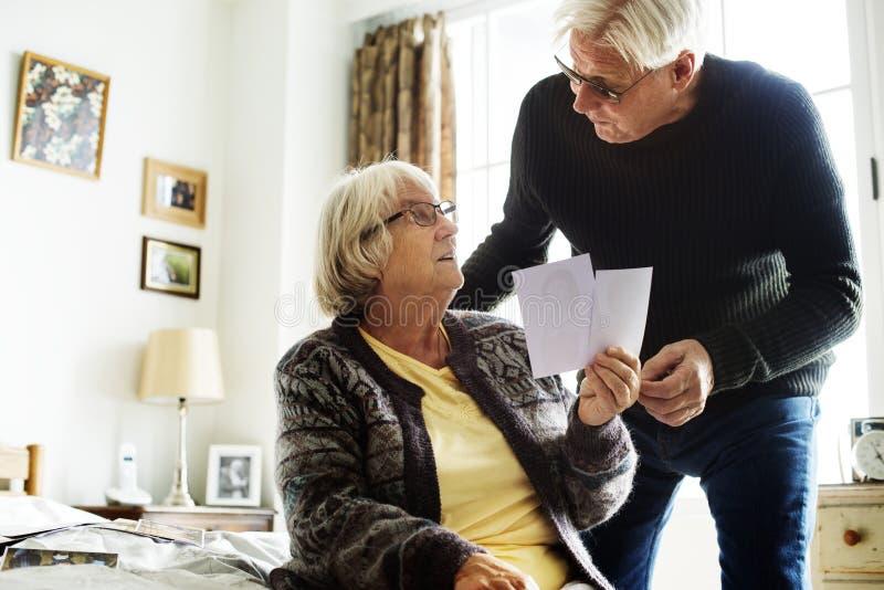 一起看照片的资深夫妇在屋子里 免版税库存图片
