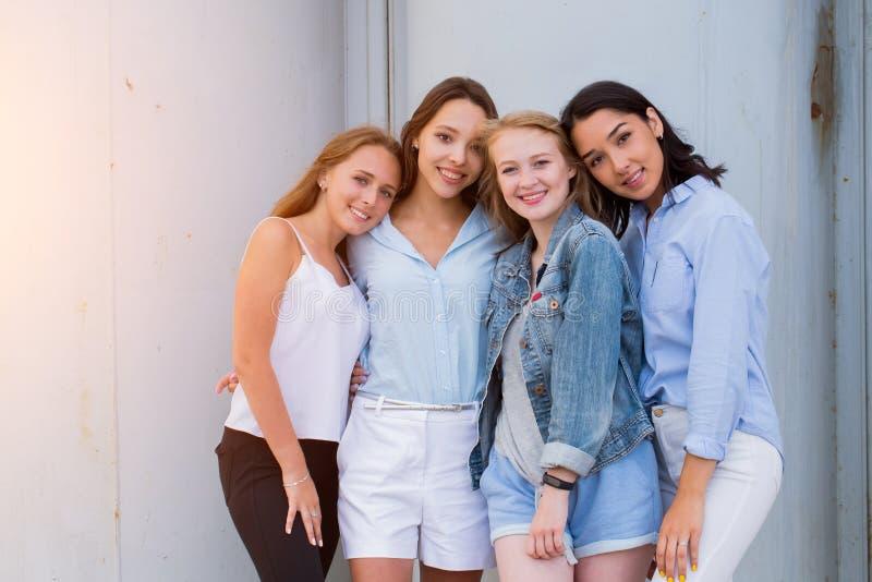 一起看照相机的四个女朋友 人们,生活方式,友谊,职业概念 图库摄影