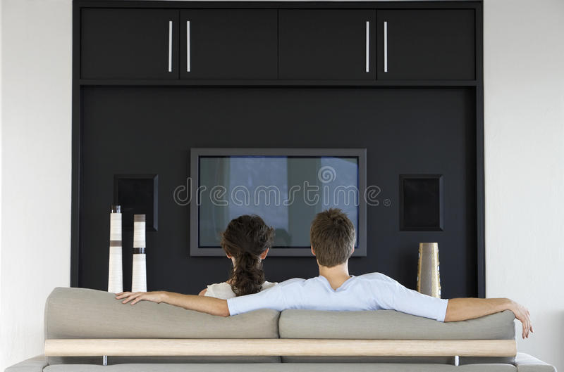 一起看电视的夫妇在客厅 库存照片