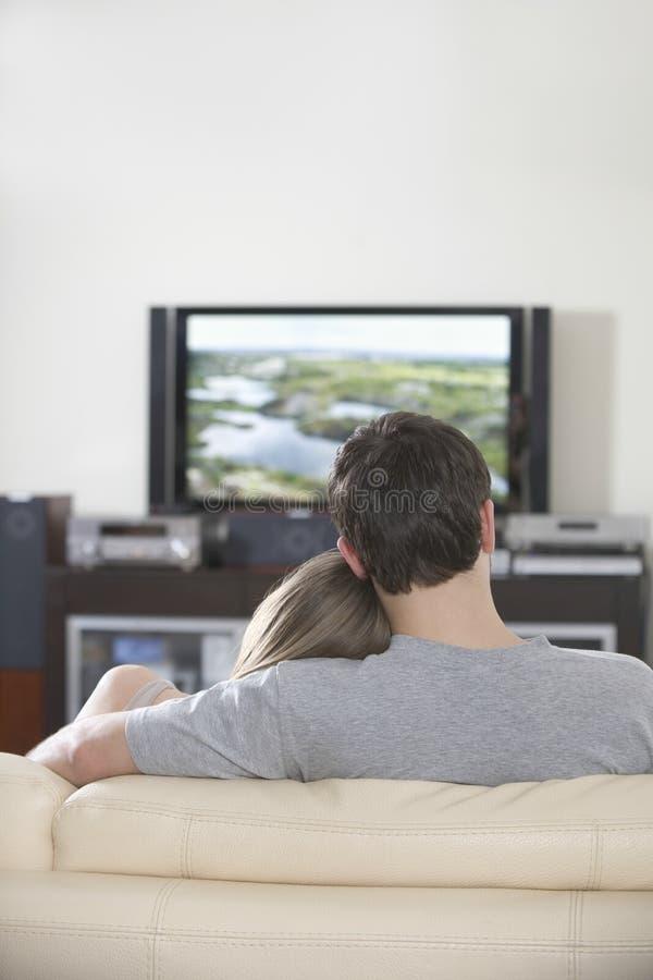 一起看电视的夫妇在家 免版税库存照片
