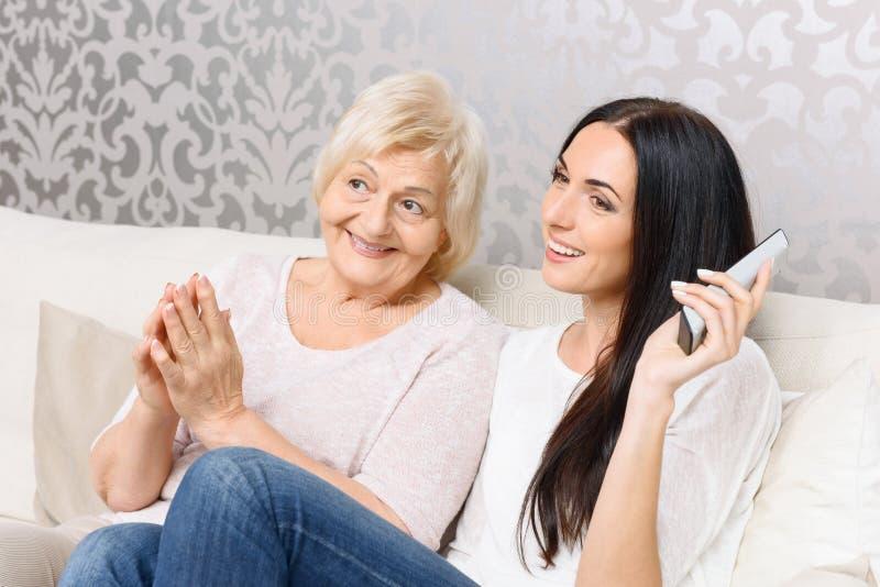 一起看电视的孙女和老婆婆 免版税库存图片
