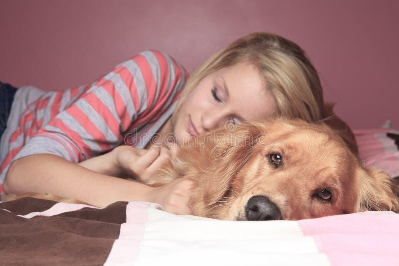 一起睡觉在卧室的女孩和她的狗 库存照片