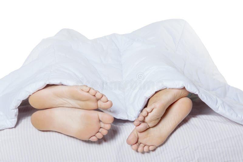 一起睡觉在床上的年轻夫妇 图库摄影