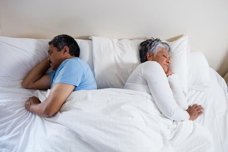 一起睡觉在床上的资深夫妇在卧室 库存照片