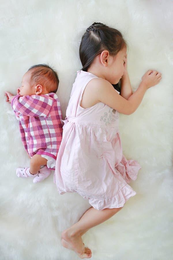 一起睡觉在白色毛皮背景的亚裔姐姐和新生儿男孩 图库摄影