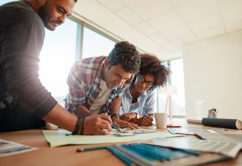 一起研究一个创造性的项目的年轻设计师 免版税库存图片