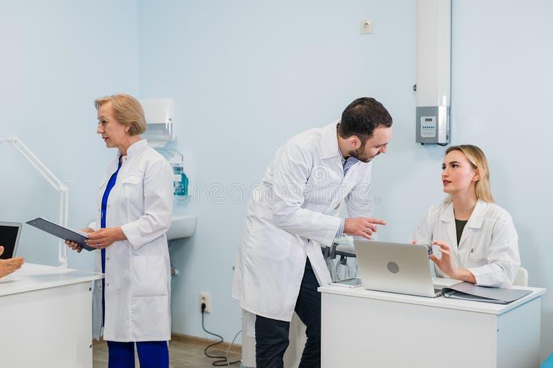一起研究一台膝上型计算机的小组医生在一个现代办公室 库存图片