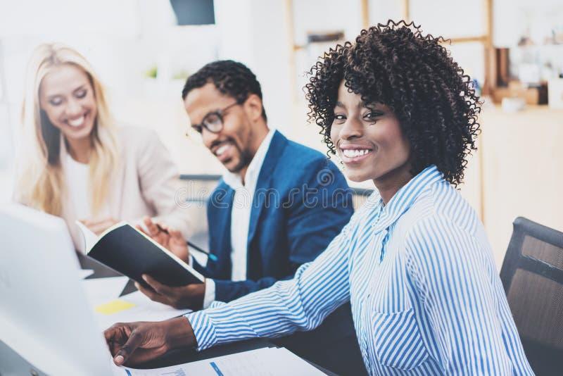 一起研究企业项目的小组三个工友在现代办公室 微笑年轻可爱的非洲的妇女,配合co 库存照片