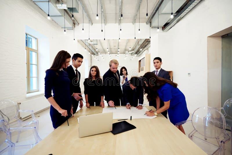 一起研究联合规划的多族群年轻设计师和建筑师,当站立在现代内部时, 免版税库存图片