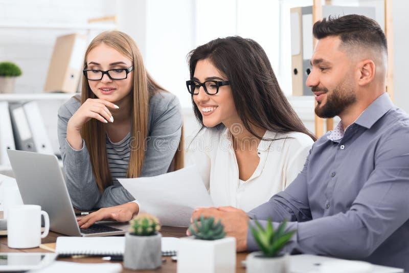 一起研究膝上型计算机的三位设计师在办公室 免版税图库摄影
