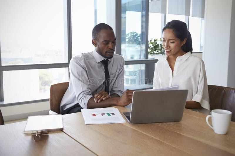 一起研究膝上型计算机的买卖人在会议室里 库存图片