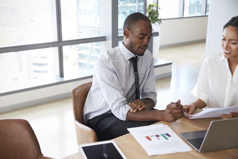 一起研究膝上型计算机的买卖人在会议室里 库存照片