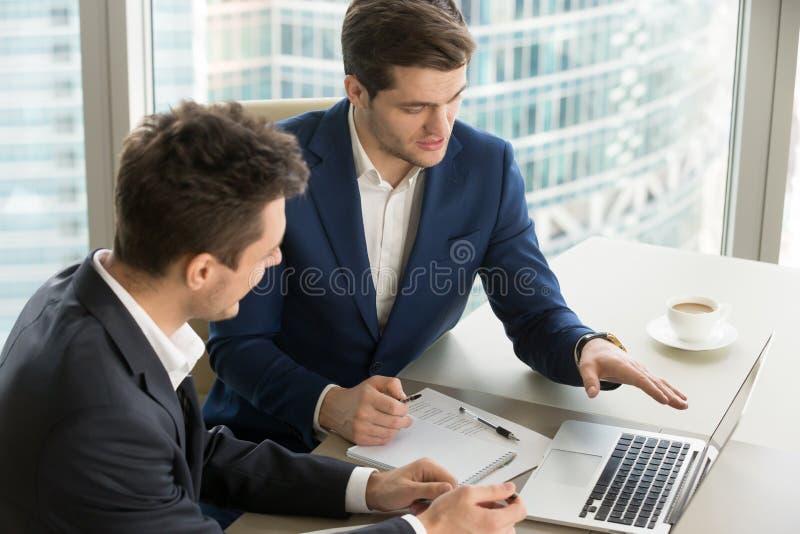 一起研究膝上型计算机的公司CEO在办公室 免版税库存照片