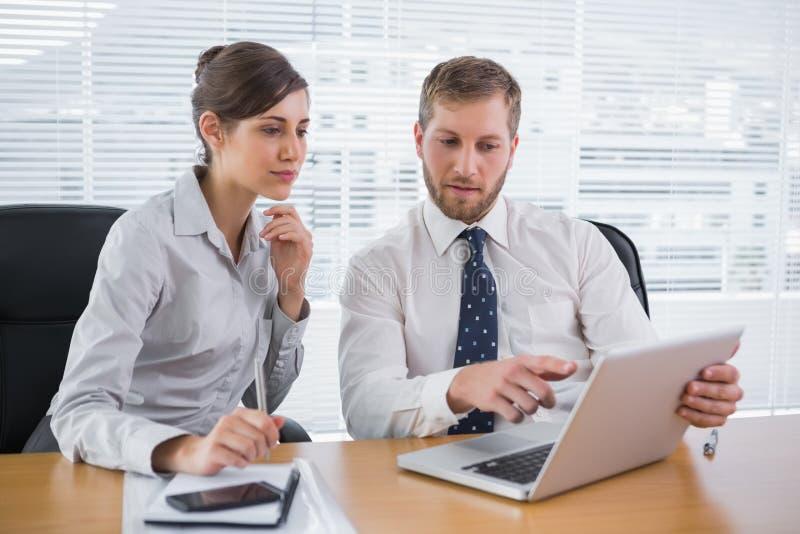 一起研究膝上型计算机的商人 免版税库存图片