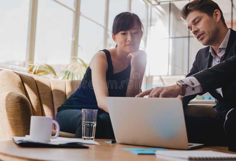 一起研究膝上型计算机的商务伙伴在办公室 库存图片