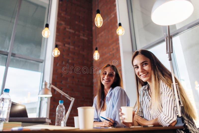 一起研究项目的三位微笑的女性大学生在教室 免版税库存图片
