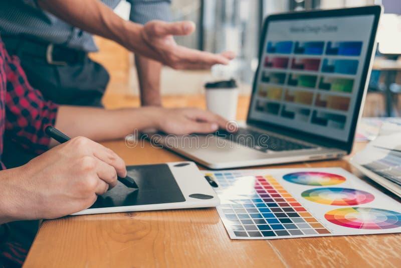 一起研究项目的年轻创造性的设计师配合和选择颜色选择着色的样片样品在数字 库存图片