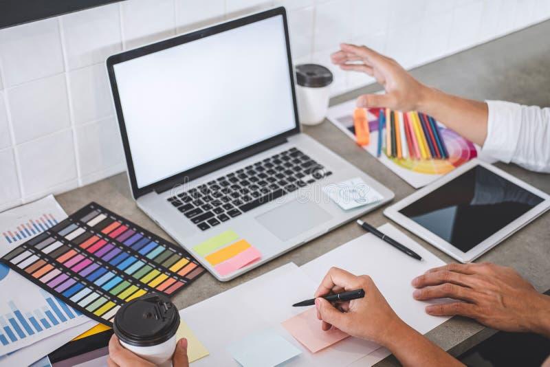 一起研究项目的年轻创造性的设计师配合和选择颜色选择着色的样片样品在数字 免版税库存图片