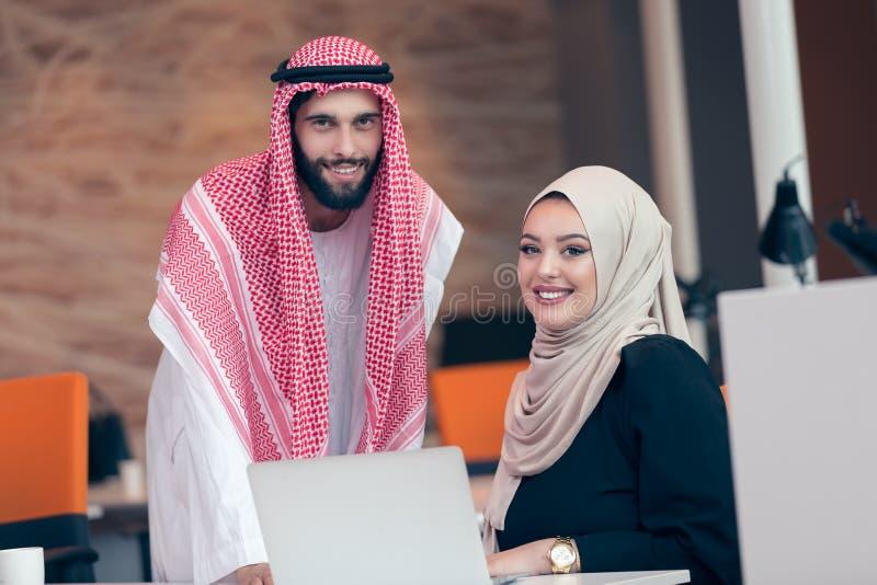 一起研究项目的阿拉伯企业夫妇在现代起始的办公室 库存照片