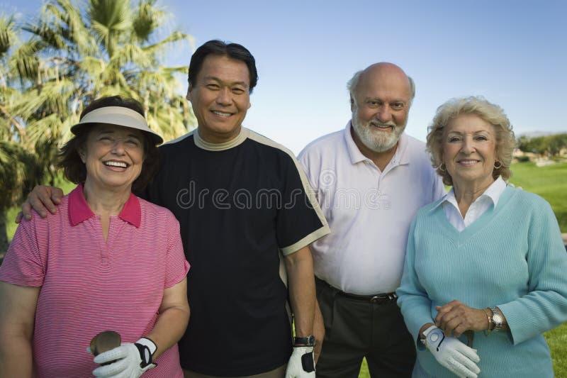 一起站立不同种族的高尔夫球运动员 库存图片
