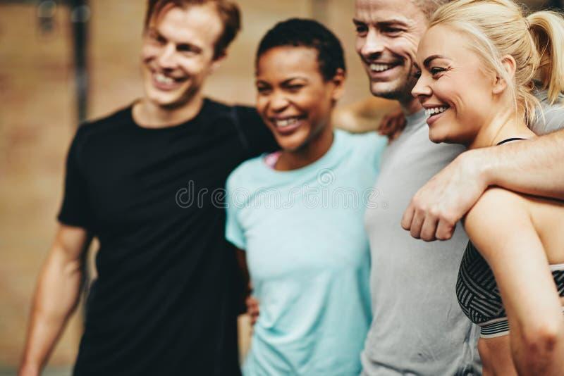 一起站立在健身房的微笑的小组不同的朋友 免版税库存照片
