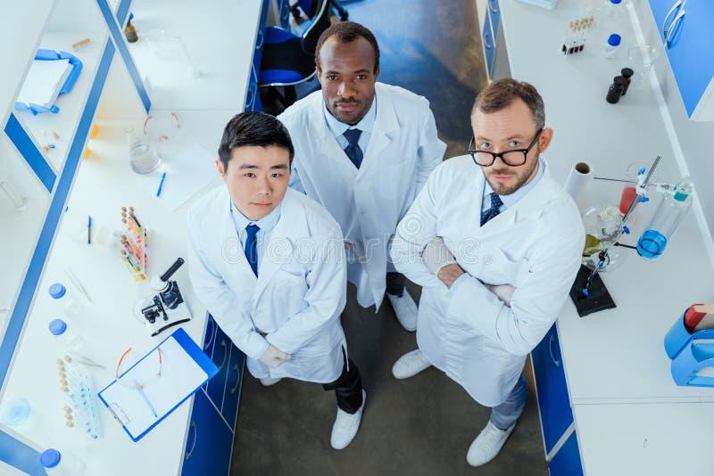 一起站立在化工实验室的多种族小组科学家 免版税库存图片