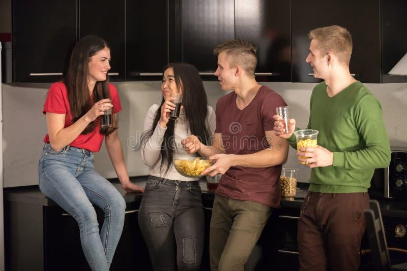 一起站立在厨房消费时间的四个年轻朋友 联系 库存照片