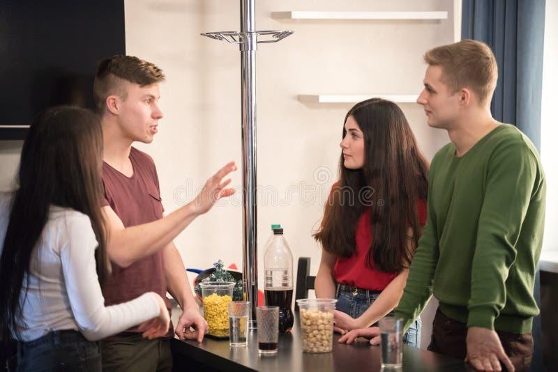 一起站立在厨房消费时间的四个年轻朋友 免版税库存照片