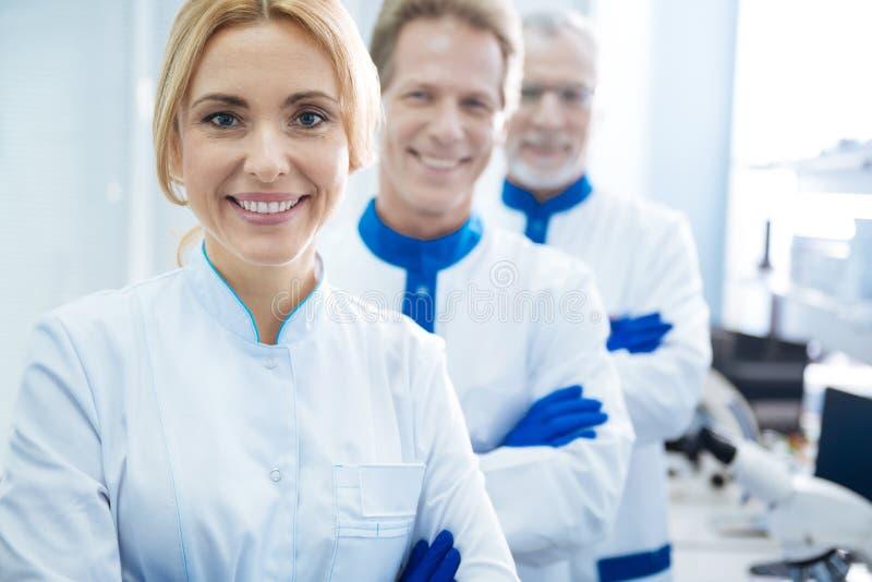 一起站立在实验室的被启发的科学家 图库摄影