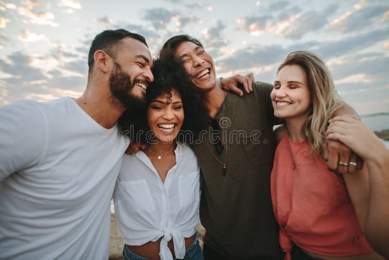 一起站立在海滩和笑的小组朋友 免版税库存图片