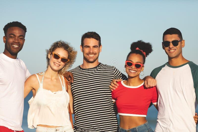 一起站立在海滩的小组愉快的朋友 免版税图库摄影