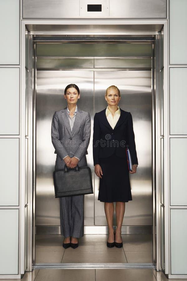一起站立在电梯的确信的女实业家 库存照片