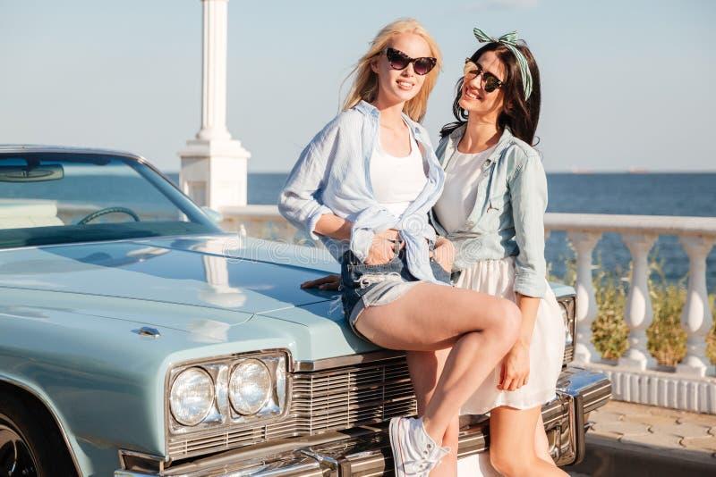 一起站立在葡萄酒汽车附近的两名微笑的妇女 免版税库存照片
