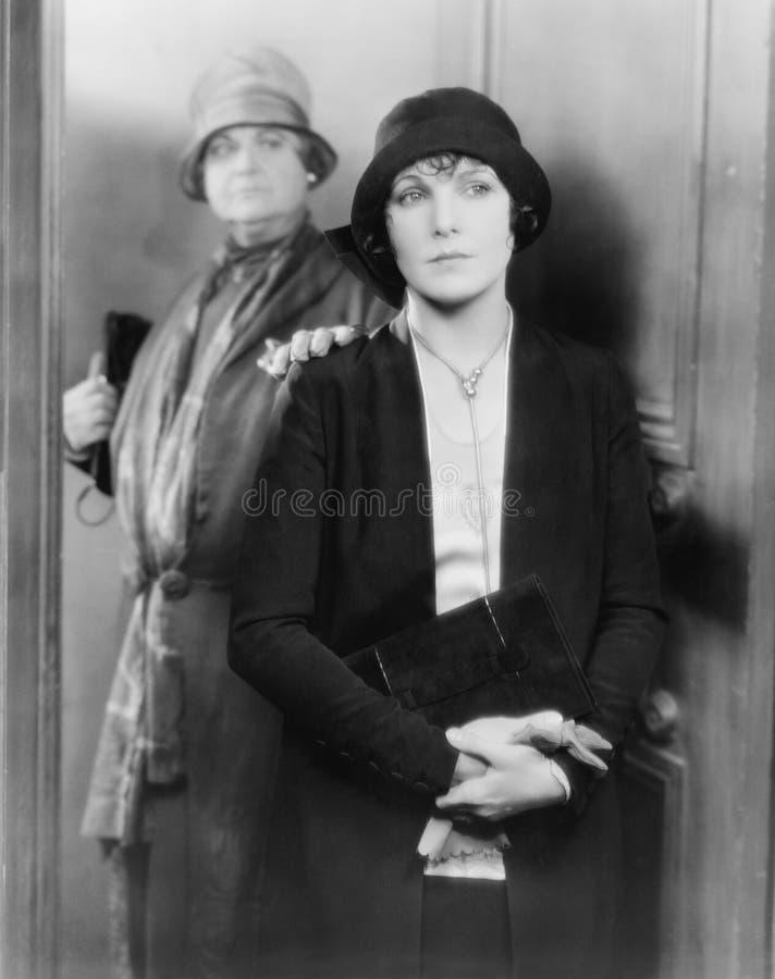 一起站立在门的两名妇女(所有人被描述不更长生存,并且庄园不存在 供应商保单那 库存照片