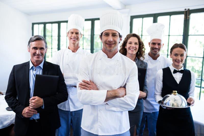 一起站立在餐馆的愉快的餐馆队 免版税库存照片