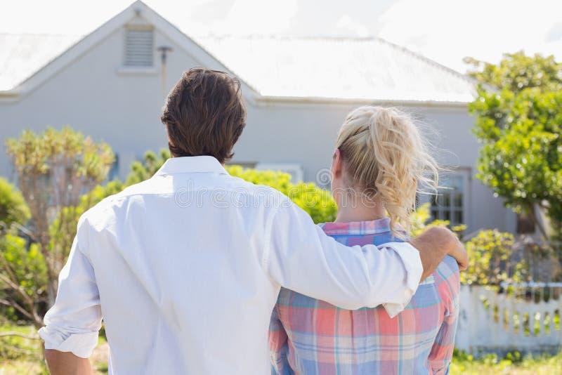 一起站立在他们的庭院里的逗人喜爱的夫妇看房子 免版税图库摄影