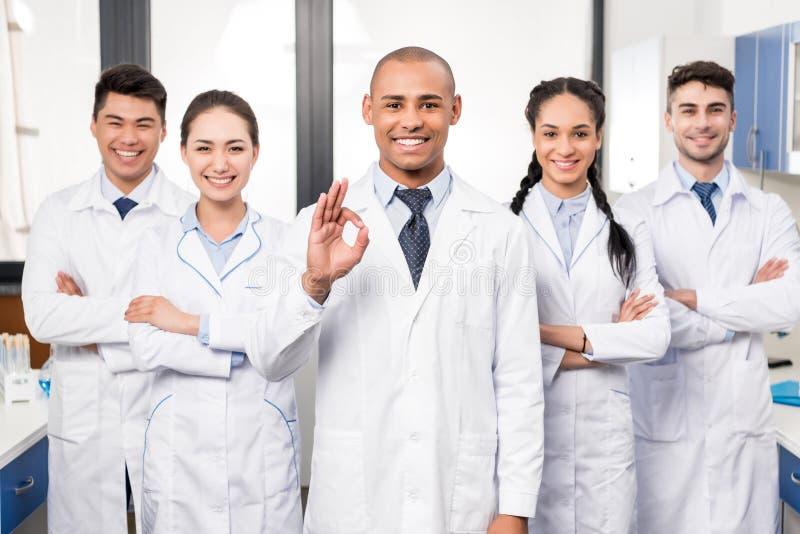 一起站立微笑的专业的医生队,当他们的领导显示得好时 图库摄影