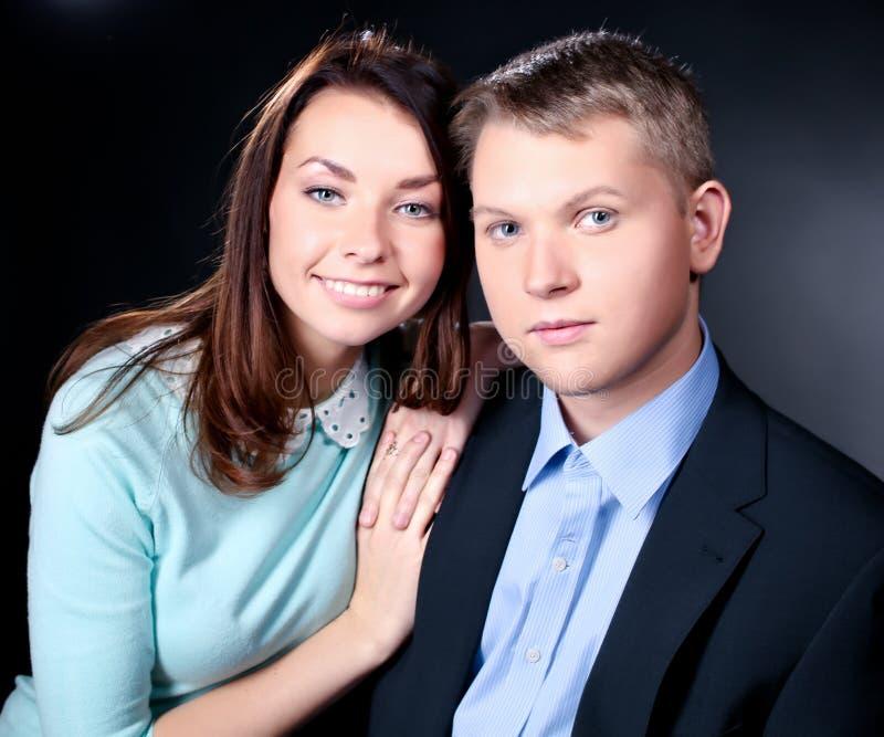 一起站立年轻的夫妇,摆在演播室 免版税库存图片