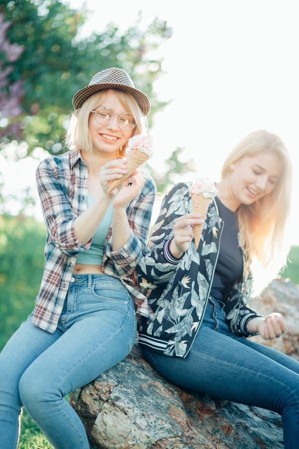 一起笑两个的最好的朋友有冰淇凌和户外 免版税图库摄影