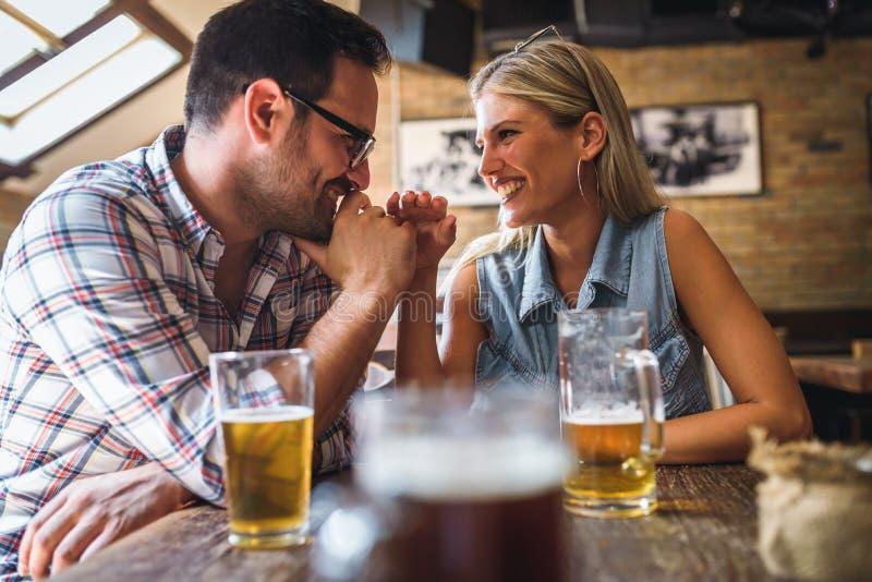 一起笑愉快的朋友获得乐趣在酒吧-年轻时髦夫妇饮用的啤酒和 免版税库存照片