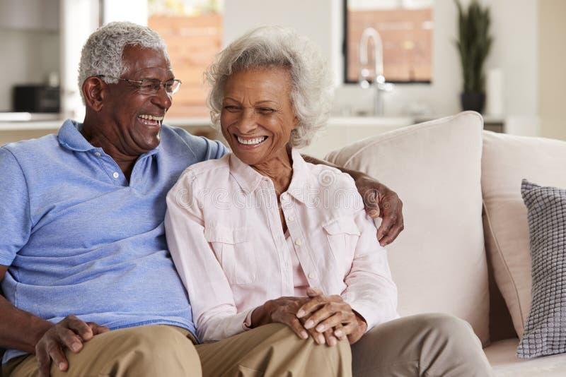一起笑爱的资深的夫妇在家坐沙发和 免版税库存图片