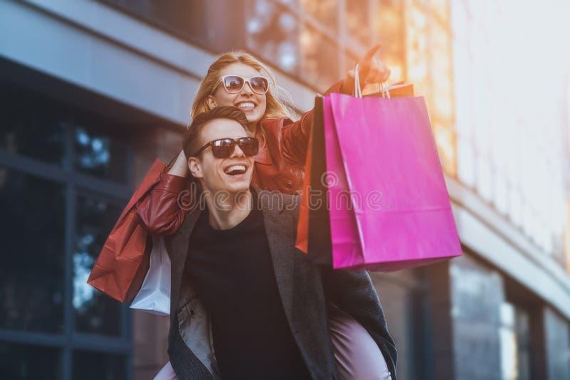 一起结合在购物 获得愉快的夫妇一起购物和乐趣 运载他的肩扛的男朋友女朋友 免版税库存照片