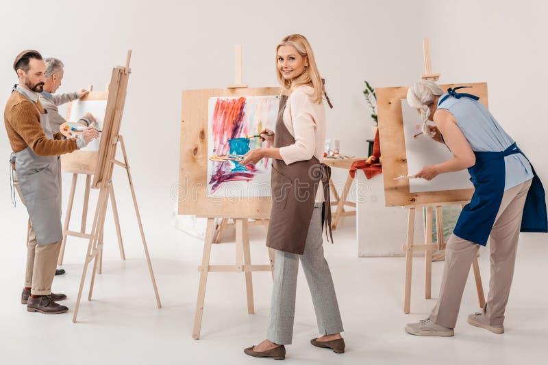 一起绘在画架的围裙的男性和女性成人学生 库存图片