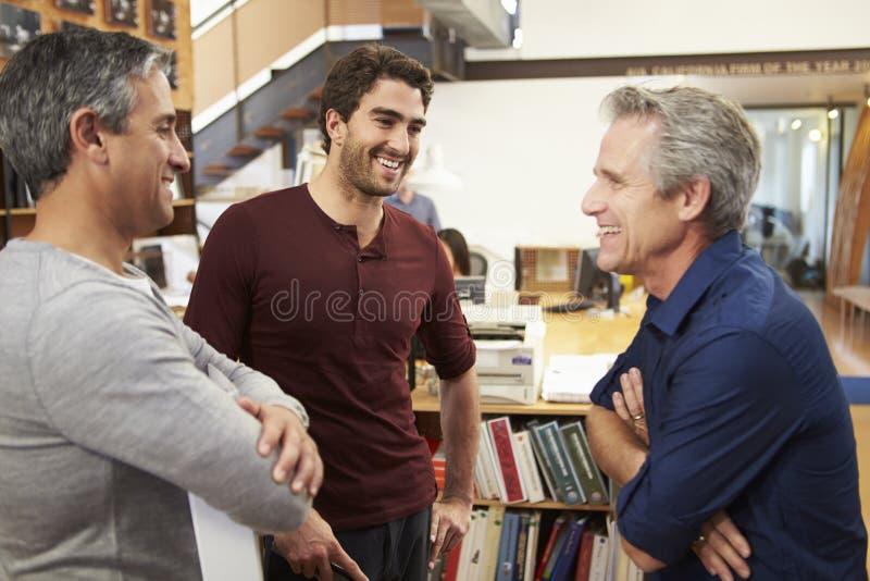 一起聊天在现代办公室的三位男性建筑师 免版税库存图片