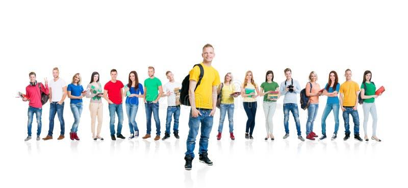 一起聚集和看照相机的大小组微笑的朋友隔绝在白色背景 免版税库存图片