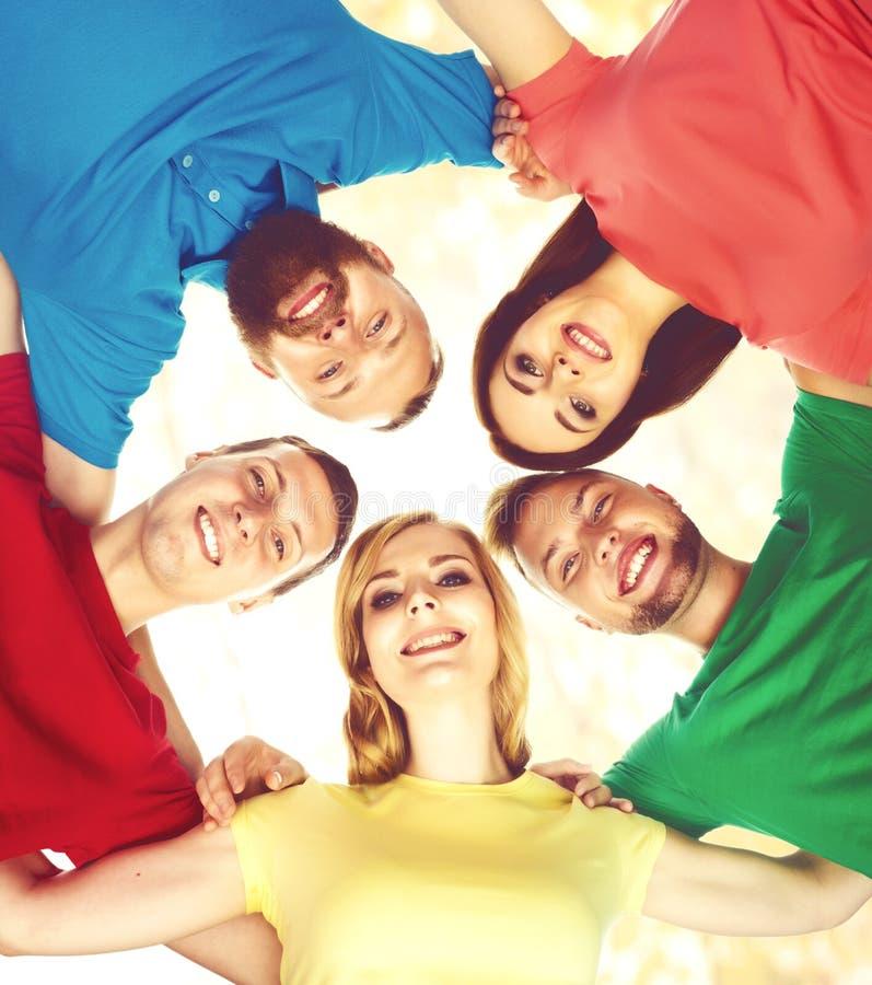 一起聚集和看c的大小组微笑的朋友 免版税库存图片
