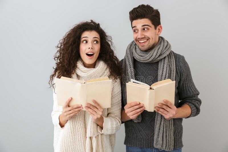 一起聪明的男人和妇女看书的图象,被隔绝在灰色背景 库存照片