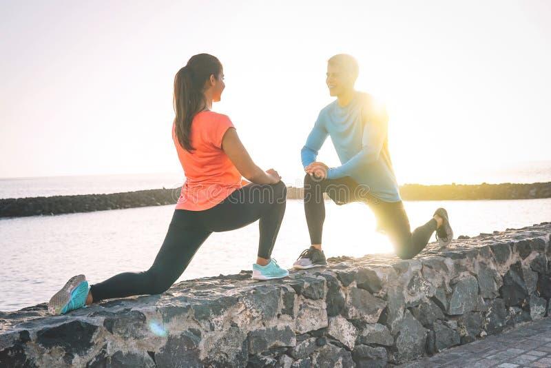 一起舒展腿的年轻健康夫妇在海滩旁边在日落-愉快的嬉戏恋人锻炼 库存图片