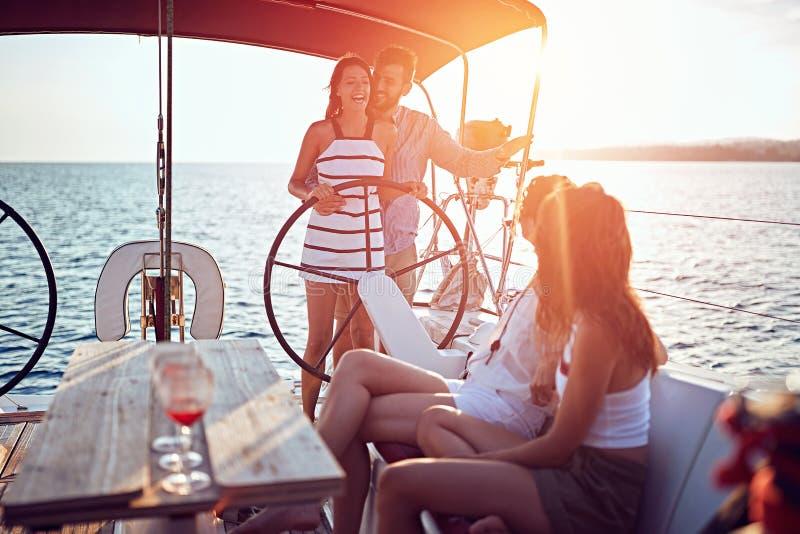 一起航行在豪华小船的年轻人和享用在日落 免版税库存照片