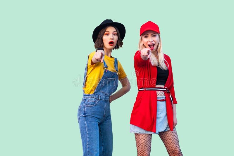一起花费了不起的时间的最好的朋友 站立和指向手指的两个美丽的惊奇时兴的行家女孩您, 免版税图库摄影